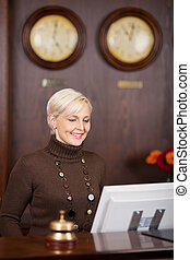 smiling female receptionist at hotel counter - smiling...