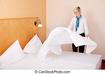 Housekeeper Making Bed In Hotel Room - Young female...