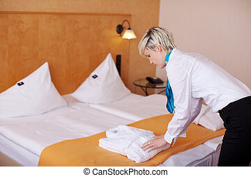 Female Housekeeper Keeping Bathrobe On Bed - Side view of...
