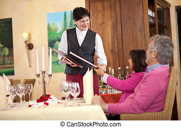 confident waitress passing the menu to couple sitting at the...