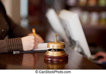 bell at hotel counter with woman filling up a formular