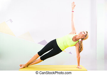 beautiful pilates instructor with yellow yoga mat - Fit...