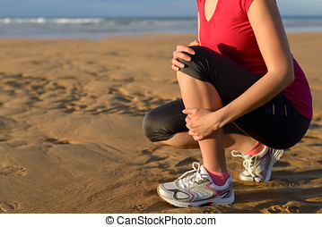 Runner injury shin splint - Female runner clutching her shin...