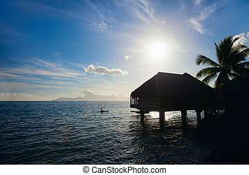 Sunset at Tahiti - Silhouette of overwater bungalow at...