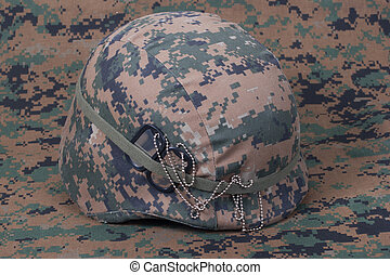 kevlar helmet with dog tags on camouflage cover