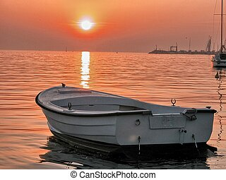 Isolated small boat at summer sunset.