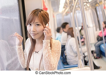 Asian beauty in MRT carriages use her cellphone, Taipei,...