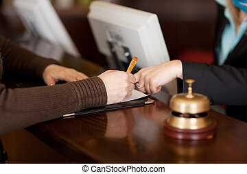 Receptionists Assisting Female Customer In Filling Up Form -...