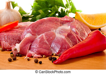 Fresh raw pork on board with fresh, vegetables. Isolated on...