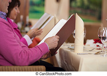 couple in restaurant reading the menu - couple in restaurant...