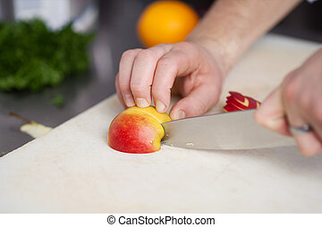 Chefs Hands Cutting An Apple On Chopping Board - Closeup of...