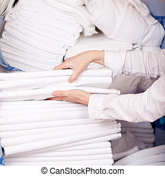 Housekeeper's Hands Stacking Sheet - Closeup of female...