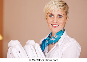 Smiling Female Housekeeper With Bathrobes - Portrait of...