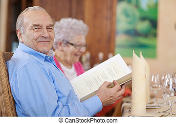 smiling senior couple in restaurant with menu in hand