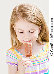 Cute blond little girl eating ice-cream in summer sunny day