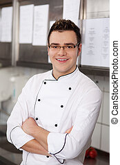 confident smiling cook in restaurants kitchen