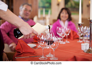 waitress pouring red wine at guestacute;s glasses -...