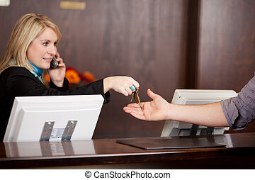 Young Receptionist Giving Room Keys To Customer - Young...