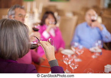group of aged friends drinking red wine in restaurant