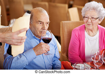 senior man tasting the wine in restaurant, sitting at table