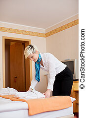 Housekeeper Keeping Bathrobe On Bed - Side view of young...