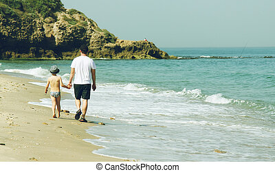 father and son walking together on the beach