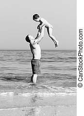 Happy father and son on the beach. black and white photo....