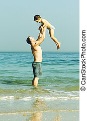 Happy father and son on the beach. Photo in old image color....