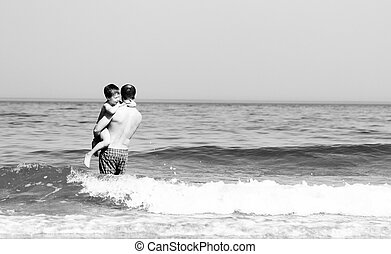 father and son going to swim in the sea black and white...