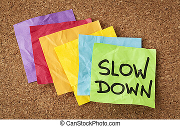 slow down - lifestyle concept or advice - handwriting on...