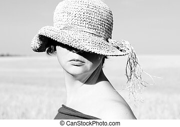 Pretty woman in the hat in the field Black and white photo...