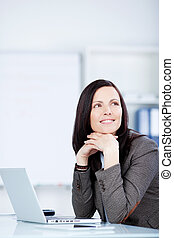 Pensive woman sitting at her desk