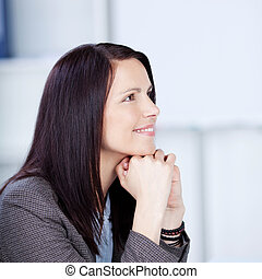 Young woman sitting daydreaming