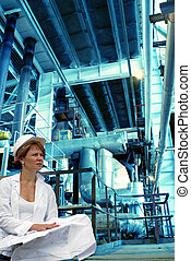 woman engineer, equipment, cables and piping as found inside...