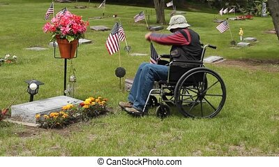 man at cemetery - disabled man in a wheelchair at the...