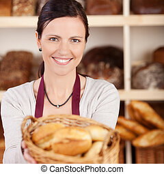 Beautiful female bakery worker with a charming friendly...