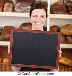 Bakery worker holding a blank chalkboard - Beautiful smiling...