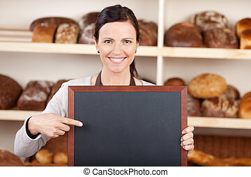 Worker in a bakery pointing to a blank board - Pretty worker...