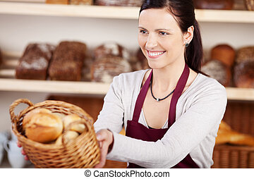 Woman working in a bakery offering a customer a basket of...