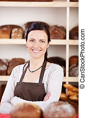 Owner of a bakery standing with folded arms - Attractive...