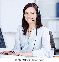 Pretty call center operator typing on the keyboard at her...
