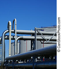 industrial pipelines and storage tanks against blue sky