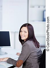Charming businesswoman working in front of her computer