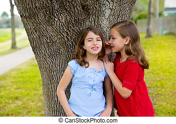 kid friend girls whispering ear playing in a park tree -...