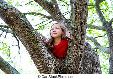 children kid girl playing climbing to a tree in a park...