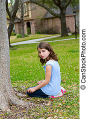 beautiful kid girl smiling sitting on park lawn relaxed