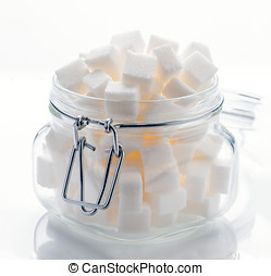 glass jar full of white sugar cubes on white base