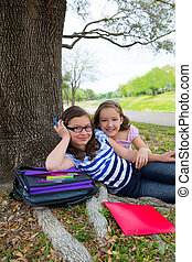 sister friends girls relaxed under tree park after school