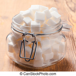 glass jar full of white sugar cubes on wooden base rustic
