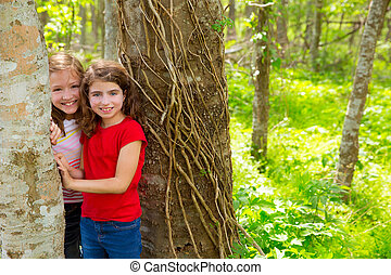children friends playing in tree trunks at the jungle park